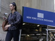 A woman passes an entrance of the New York Stock Exchange, Wednesday, June 16, 2021. Stocks are opening broadly lower on Wall Street, putting the S&P 500 index on track for its first losing week in the last four. The benchmark index gave up 0.8% in the early going Friday, June 18 with banks and technology companies leading the way lower.