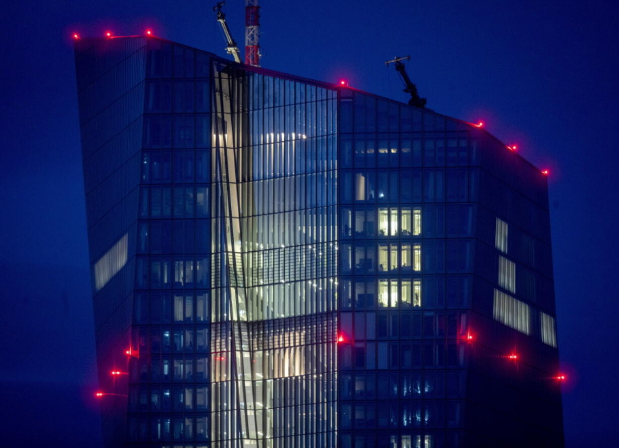 FILE - In this Oct.5,2020 file photo red warning lights shine on the building of the European Central Bank in Frankfurt, Germany. The European Central Bank is expected to leave its stimulus efforts running full steam Thursday -- even as the economy in the 19 countries that use the euro currency shows more and more signs of a robust recovery as pandemic restrictions ease.