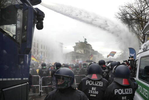 File - In this Wednesday, Nov. 18, 2020 file photo, police uses water canons to clear a blocked a road between the Brandenburg Gate and the Reichstag building, home of the German federal parliament, as people attend a protest rally in Berlin, Germany, against the coronavirus restrictions in Germany. Authorities in Germany say the number of far-right extremists in the country increased last year as neo-Nazis sought to join protests against pandemic-related restrictions. German Interior Minister Horst Seehofer said authorities counted 33,300 far-right extremists in 2020, an increase of almost 4% from the previous year.