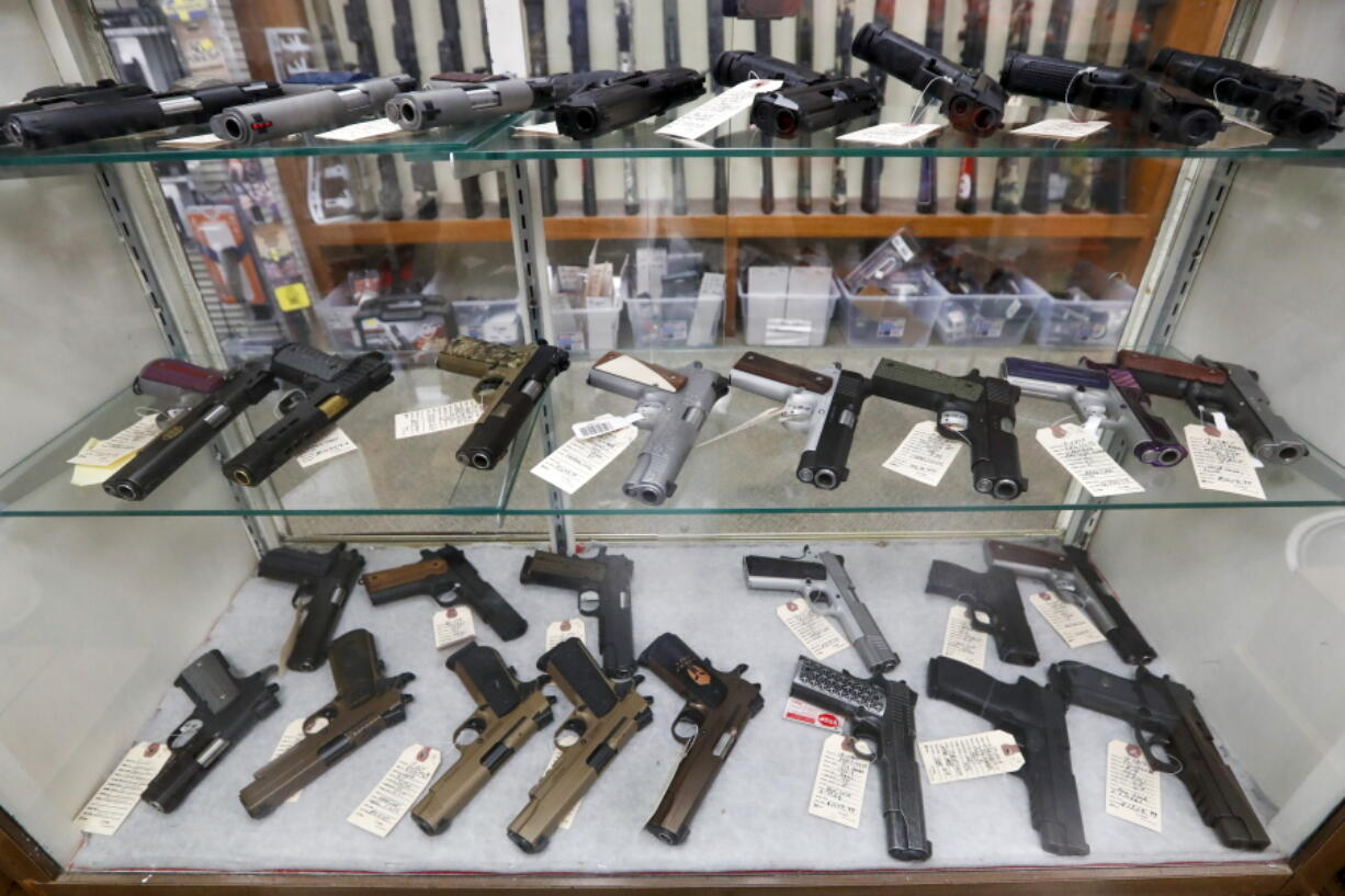 FILE - In this March 25, 2020, file photo semi-automatic handguns are displayed at shop in New Castle, Pa. The number of people stopped from buying guns though the U.S. background check system hit an all-time high of more than 300,000 last year amid a surge of firearm sales, according to new records obtained by the group Everytown for Gun Safety.  The FBI numbers provided to The Associated Press show the background checks blocked nearly twice as many gun sales in 2020 as in the year before.