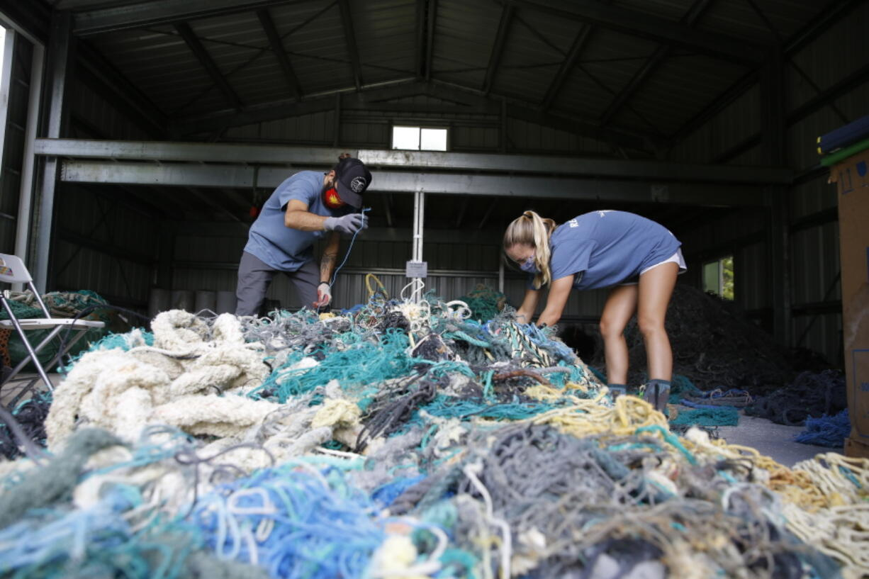 Hawaii Pacific University graduate student Drew McWhirter, left, and Raquel Corniuk, a research technician at the university's Center for Marine Debris Research, pull apart a massive entanglement of ghost nets May 12 in Kaneohe, Hawaii. The two are part of a study that is attempting to trace derelict fishing gear that washes ashore in Hawaii back to the manufacturers and fisheries that it came from.