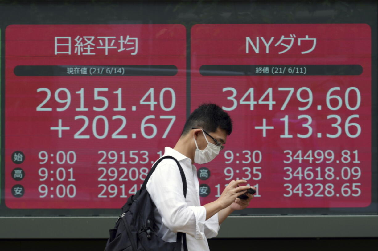 A man wearing a protective mask walks in front of an electronic stock board showing Japan's Nikkei 225 and New York Dow indexes at a securities firm Monday, June 14, 2021, in Tokyo. Asian stock markets were mixed Monday as investors looked ahead to this week's Federal Reserve meeting for hints of possible changes in ultra-low interest rates and other economic stimulus.