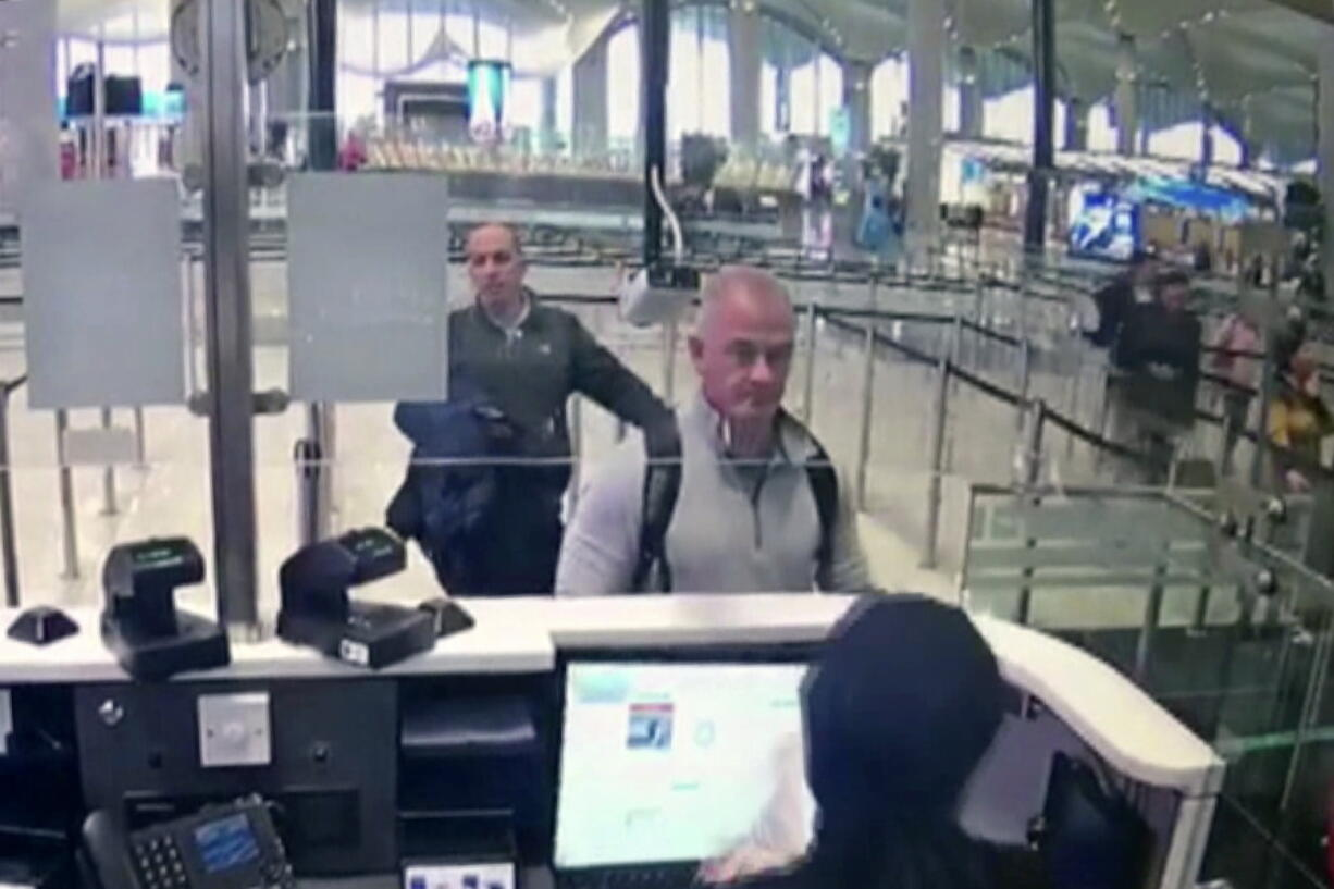FILE-- This Dec. 30, 2019 image from security camera video shows Michael L. Taylor, center, and George-Antoine Zayek at passport control at Istanbul Airport in Turkey. Americans Michael Taylor and his son Peter Taylor go on trial in Tokyo on Monday, June 14, 2021, on suspicion they helped Nissan former Chairman Carlos Ghosn skip bail in Japan and escape to Lebanon in December 2019.