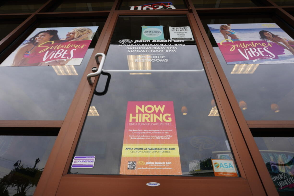 A Now Hiring sign at a business in Richmond, Va., Wednesday, June 2, 2021.  U.S. employers posted a record 9.3 million job openings in April as the U.S. economy reopens at break-neck speed. Openings were up 12 percent from 8.3 million in March.