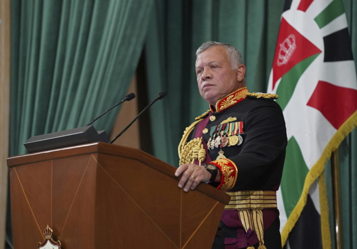 FILE - In this Dec. 10, 2020 file photo released by the Royal Hashemite Court, Jordan's King Abdullah II gives a speech to parliament, in Amman Jordan. Jordan's version of a trial of the century gets under way as early as Monday, June 21, 2021. A relative of King Abdullah II and a former chief of the royal court will be ushered into the defendants' cage at the state security court to face sedition charges. They are accused of conspiring with Prince Hamzah, a half-brother of the king, to foment unrest against the monarch.