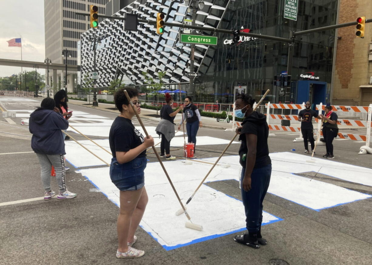 """Students from University Prep Art Design celebrate Juneteenth by repainting a street mural, """"Power To The People,"""" in downtown Detroit on Saturday,  June 19, 2021."""