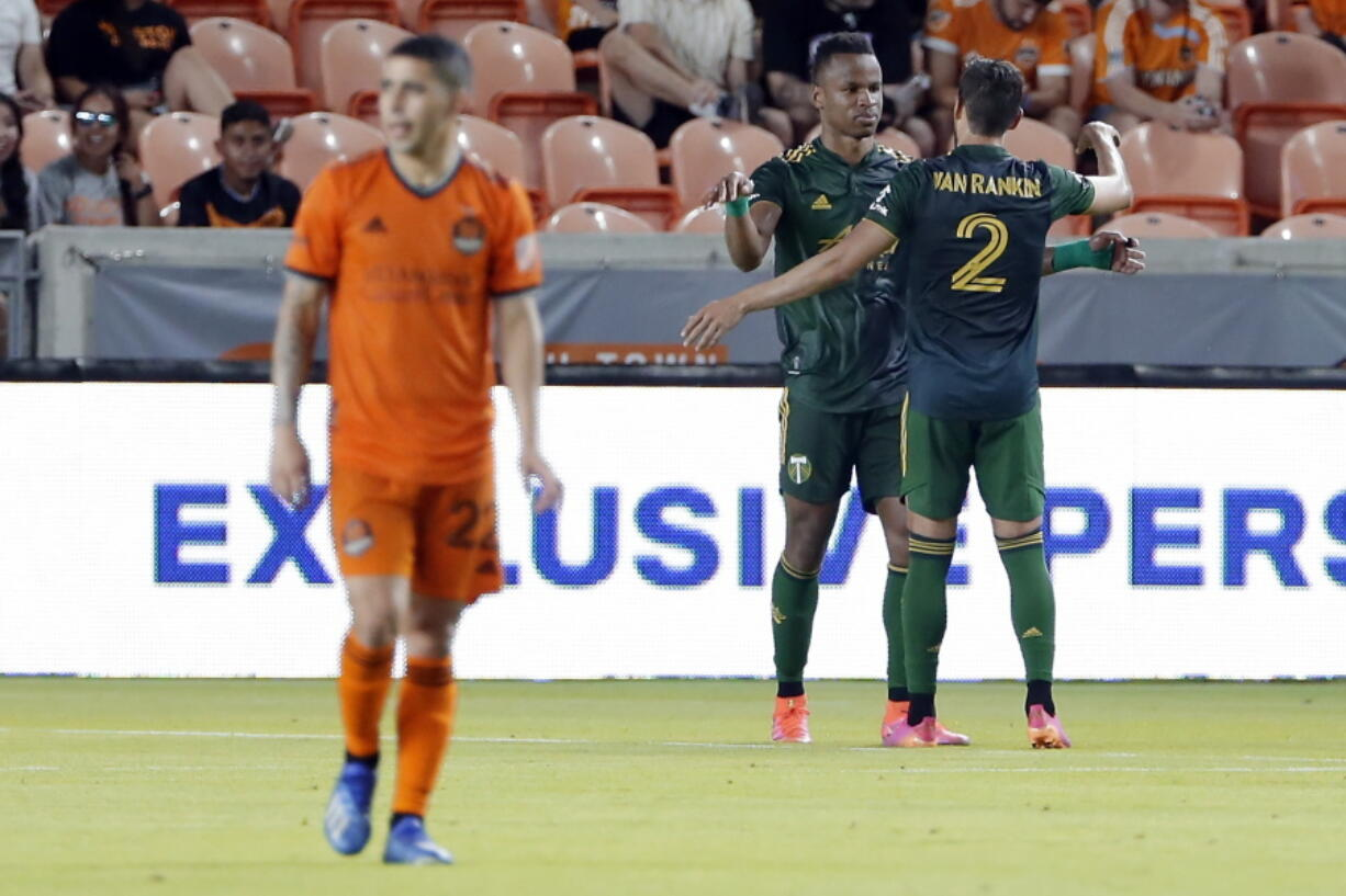 Houston Dynamo midfielder Matias Vera (22) walks off as Portland Timbers Jeremy Ebobisse, middle, and Jose van Rankin (2) celebrate the goal by Ebobisse during the second half of an MLS soccer match Wednesday, June 23, 2021, in Houston.