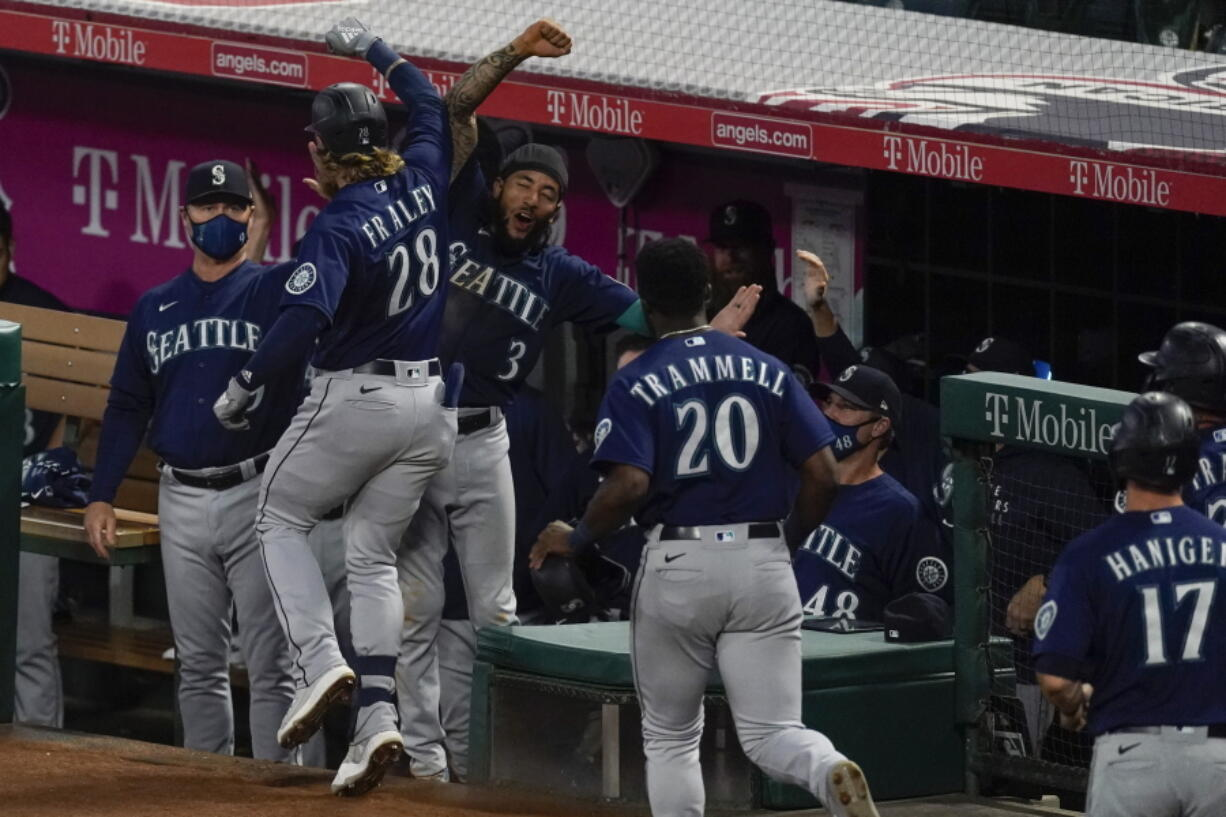 Seattle Mariners designated hitter Jake Fraley (28) celebrates with J.P. Crawford (3) after hitting a grand slam home run during the fourth inning of a baseball game against the Los Angeles Angels Saturday, June 5, 2021, in Anaheim, Calif. Mitch Haniger, Ty France, and Taylor Trammell also scored.