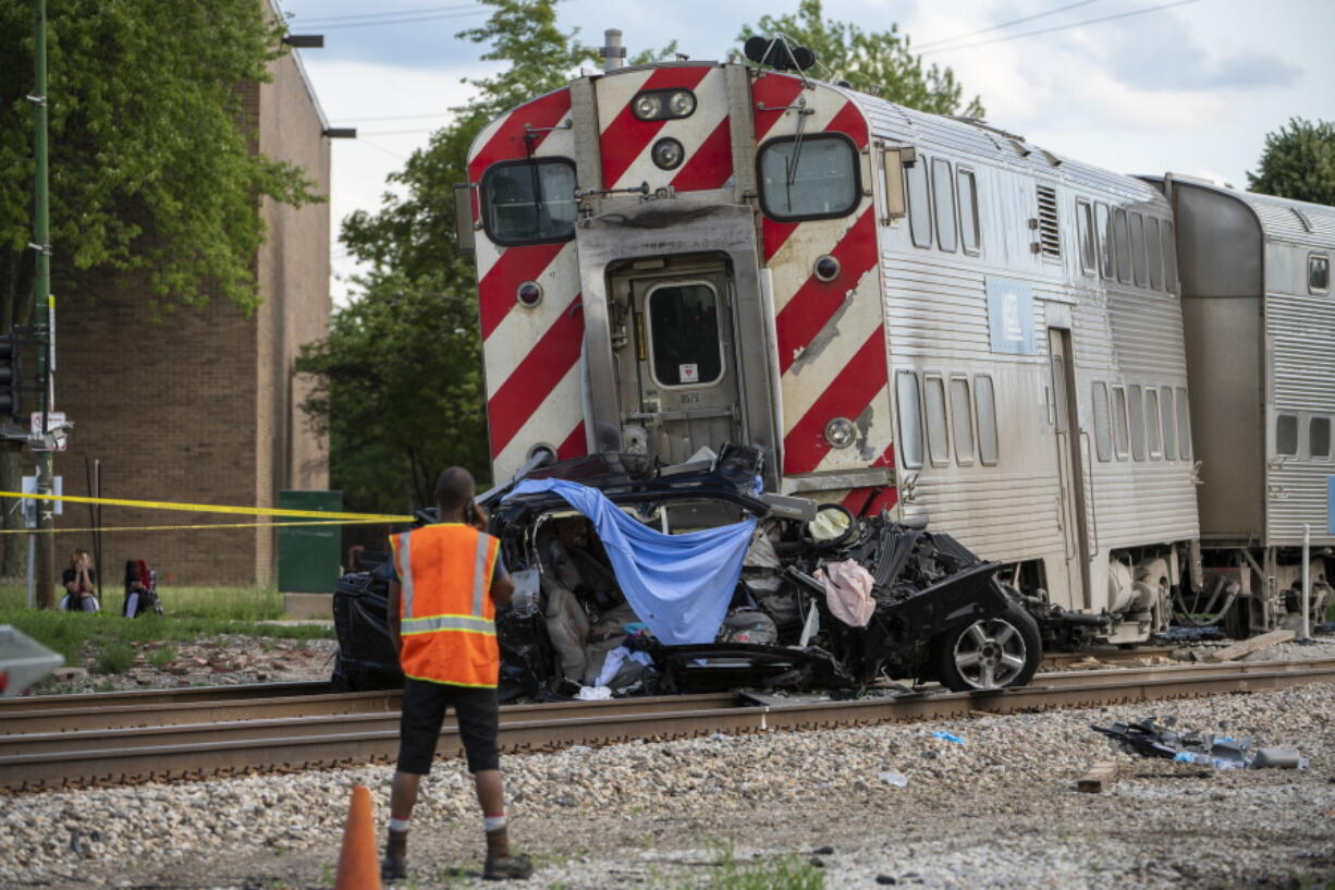 Metra police and engineers work the scene where a train collided with a vehicle, killing three occupants, including a child, in the 10300 block of South Vincennes in the East Beverly neighborhood of Chicago, Sunday, June 27, 2021.