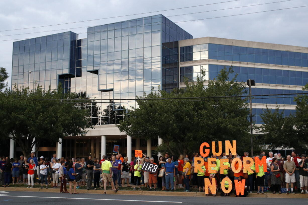 FILE - In this Aug. 5, 2019, file photo, people gather at a vigil for recent victims of gun violence outside the National Rifle Association's headquarters building in Fairfax, Va. The NRA has been embroiled in a legal and financial battle that liberals have cheered as the potential downfall of the powerful gun rights lobby, opening up a wide path for reform. Not so fast. While the battle over gun rights is shifting from Washington to the states, the NRA's message has become so solidified in the Republican political fabric that it's self-sustaining, even if the gun rights organization that led the way ceases to exist, leaders on both sides say.