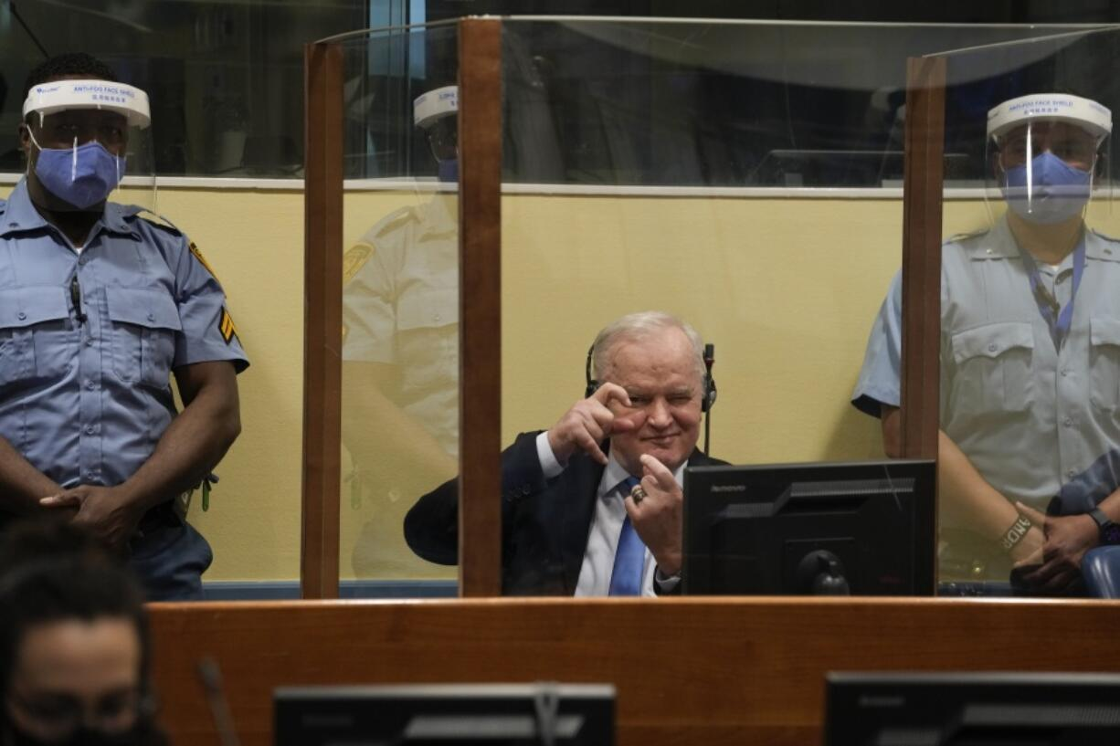 Former Bosnian Serb military chief Ratko Mladic imitates taking pictures as he sits the court room in The Hague, Netherlands, Tuesday, June 8, 2021, where the United Nations court delivers its verdict in the appeal of Mladic against his convictions for genocide and other crimes and his life sentence for masterminding atrocities throughout the Bosnian war.