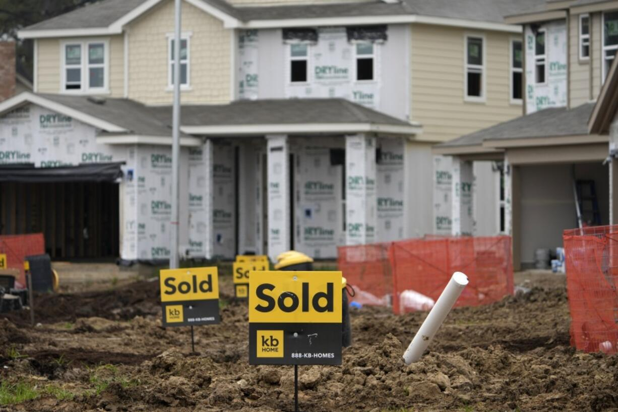Sold signs stand in front of new homes under construction Monday, March 15, 2021, in Houston.  Sales of new homes fell a bigger-than-expected 5.9% in April, a drop that analysts blamed in part on soaring home prices.  (AP Photo/David J.