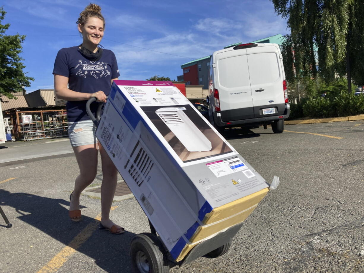 Sarah O'Sell transports her new air conditioning unit to her nearby apartment on a dolly in Seattle on Friday, June 25, 2021. O'Sell snagged one of the few AC units available at the Junction True Value Hardware as Pacific Northwest residents brace for an unprecedented heat wave that has temperatures forecasted in triple-digits.
