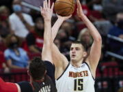 Denver Nuggets center Nikola Jokic shoots over Portland Trail Blazers center Jusuf Nurkic during the first half of Game 6 of an NBA basketball first-round playoff series Thursday, June 3, 2021, in Portland, Ore.