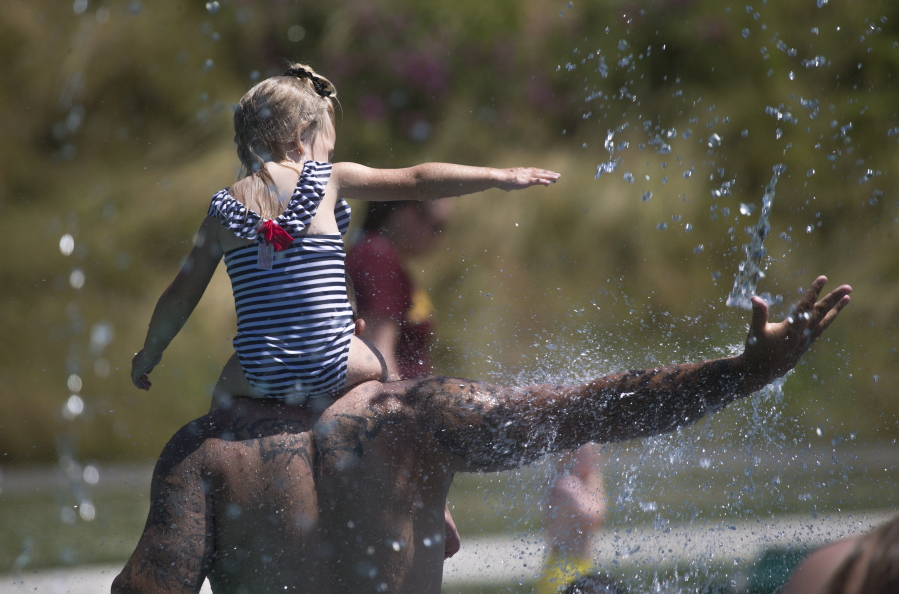 Keeping cool in record setting temperatures, Beau Jess and daughter River, 3, reach for falling water as they play at the Splash Pad in Haller Park on Monday, June 28, 2021 in Arlington, Wash.