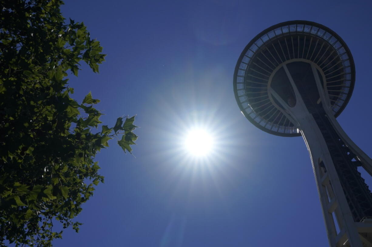 The sun shines near the Space Needle, Monday, June 28, 2021, in Seattle. Seattle and other cities broke all-time heat records over the weekend, with temperatures soaring well above 100 degrees Fahrenheit (37.8 Celsius). (AP Photo/Ted S.