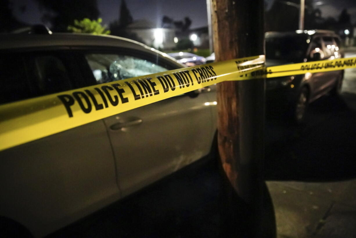 FILE - In this June 6, 2021, file photo, police respond to a multiple fatality shooting in a house in Portland, Ore. The city has seen a spike in gun violence in the past year and authorities say one reason is an increase in gang activity.