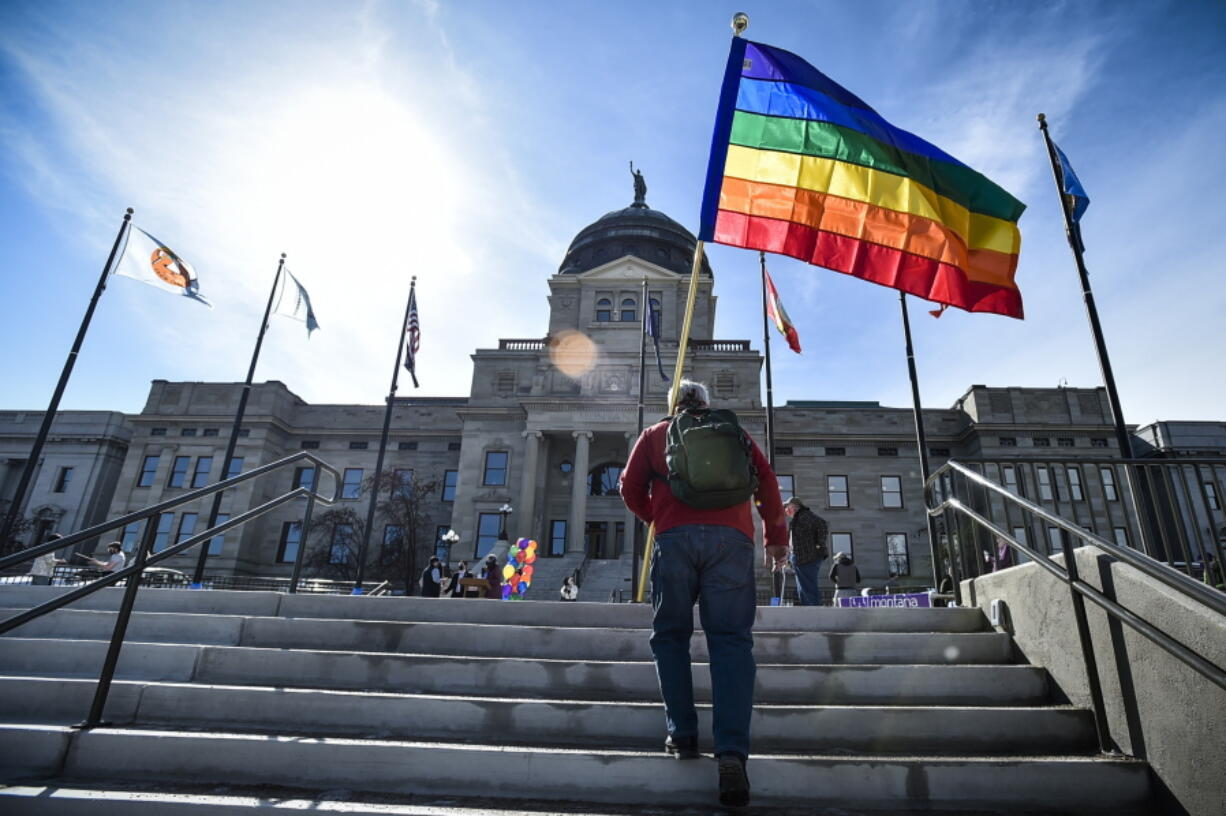 FILE - In this March 15, 2021, file photo, demonstrators gather on the steps of the Montana State Capitol protesting anti-LGBTQ+ legislation in Helena, Mont. Gov. Greg Gianforte signed a bill Friday, May 7, 2021, banning transgender athletes from participating in school and university sports according to the gender with which they identify, making Montana one of several Republican-controlled states to approve such measures in 2021.