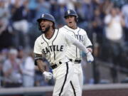 Seattle Mariners' J.P. Crawford celebrates at home with Dylan Moore behind, after hitting a grand slam off Tampa Bay Rays starting pitcher Josh Fleming during the second inning of a baseball game Saturday, June 19, 2021, in Seattle.