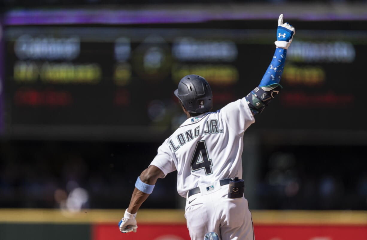 Seattle Mariners' Shed Long Jr. celebrates as he rounds the bases after hitting a grand slam off Tampa Bay Rays relief pitcher Diego Castillo that also scored Luis Torrens, Dylan Moore and Jake Bauers during the 10th inning of a baseball game, Sunday, June 20, 2021, in Seattle.