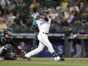 Seattle Mariners' Shed Long Jr. hits a solo home run on a pitch from Colorado Rockies' Tyler Kinley during the eighth inning of a baseball game, Tuesday, June 22, 2021, in Seattle.