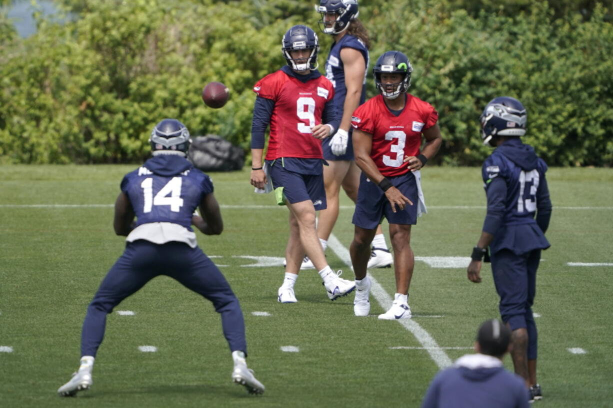Seattle Seahawks quarterback Russell Wilson (3) passes to wide receiver DK Metcalf (14) during NFL football practice Tuesday, June 8, 2021, in Renton, as quarterback Danny Etling (9) and wide receiver Darvin Kidsy (23) look on. (AP Photo/Ted S.