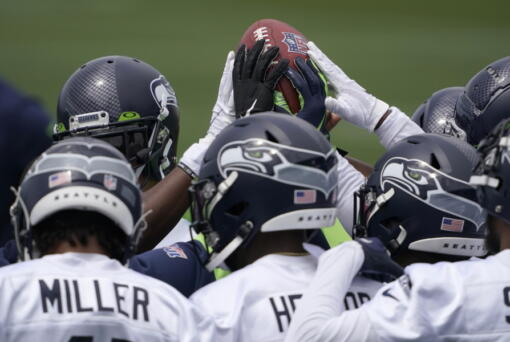 Seattle Seahawks defensive players touch the football during a huddle at NFL football practice Tuesday, June 15, 2021, in Renton, Wash. (AP Photo/Ted S.