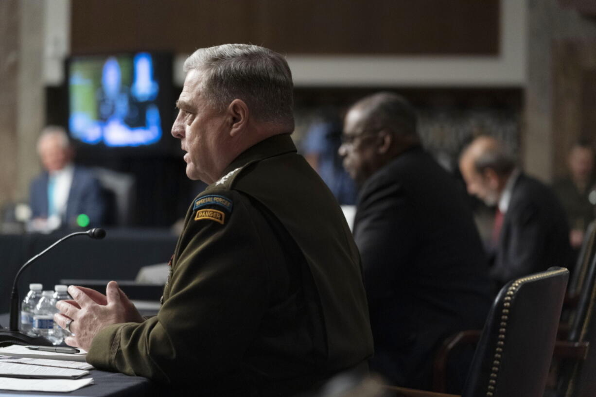 From left, Chairman of the Joint Chiefs of Staff Gen. Mark Milley, accompanied by Secretary of Defense Lloyd Austin, and Defense Under Secretary Mike McCord, speaks at a Senate Armed Services budget hearing on Capitol Hill in Washington, Thursday, June 10, 2021.
