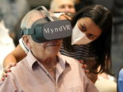 Gloria Gantes, right, monitors Terry Colli, a resident of John Knox Village, as he participates in a virtual reality study, Tuesday, June 1, 2021, in Pompano Beach, Fla. The senior community is in partnership with Stanford University's Virtual Human Interaction Lab on a study to see how older adults respond to virtual reality and whether it can improve their sense of wellbeing.
