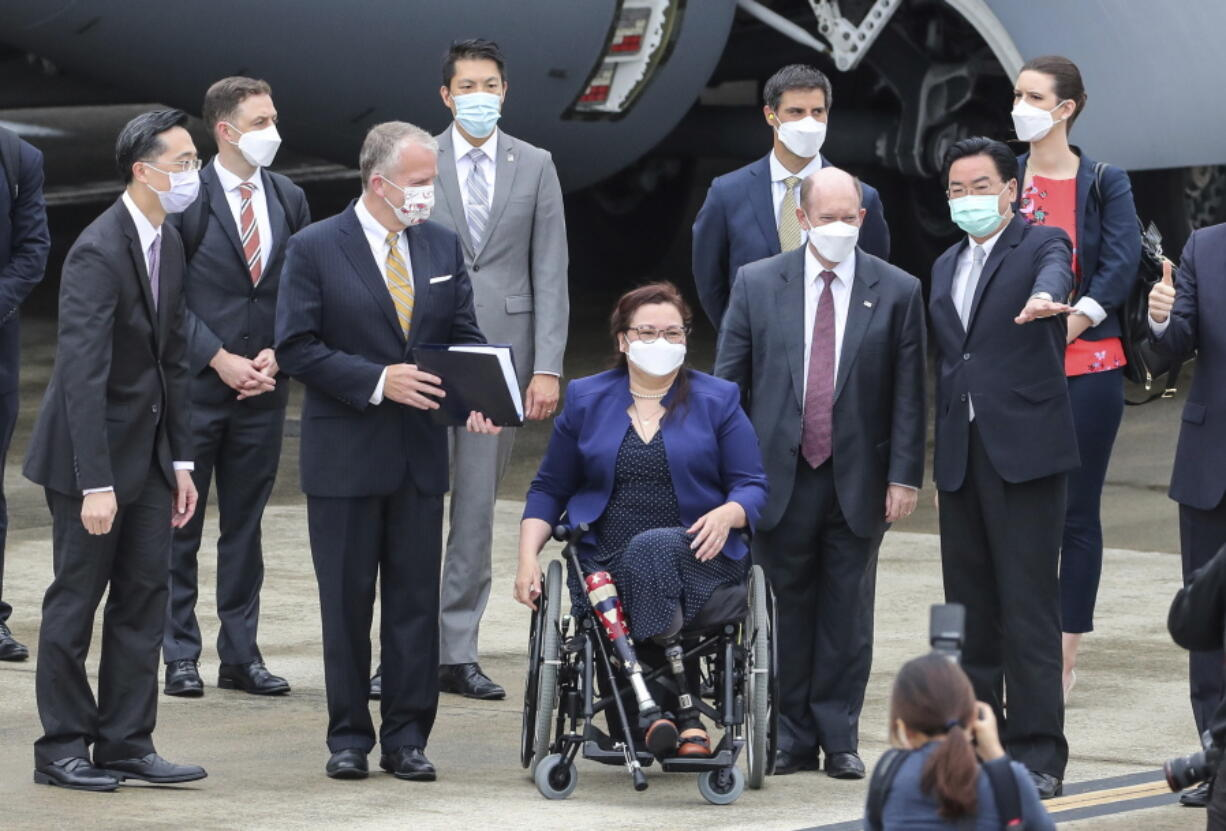 Taiwan's Foreign Minister Joseph Wu, second right, gestures as he welcomes U.S. senators to his right Democratic Sen. Christopher Coons of Delaware, a member of the Foreign Relations Committee, Democratic Sen. Tammy Duckworth of Illinois and Republican Sen. Dan Sullivan of Alaska, members of the Armed Services Committee on their arrival at the Songshan Airport in Taipei, Taiwan on Sunday, June 6, 2021. The three U.S. senators arrived in Taiwan to meet with senior government officials and discuss U.S.-Taiwan relations and other issues in a trip that is likely to anger China, which claims Taiwan as its territory and objects to Taiwan being called a country.