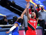Portland Trail Blazers guard Damian Lillard (0) shoots a 3-point basket against Denver Nuggets guard Shaquille Harrison (3) to send Game 5 of a first-round NBA basketball playoff series into a second overtime, Tuesday, June 1, 2021, in Denver.