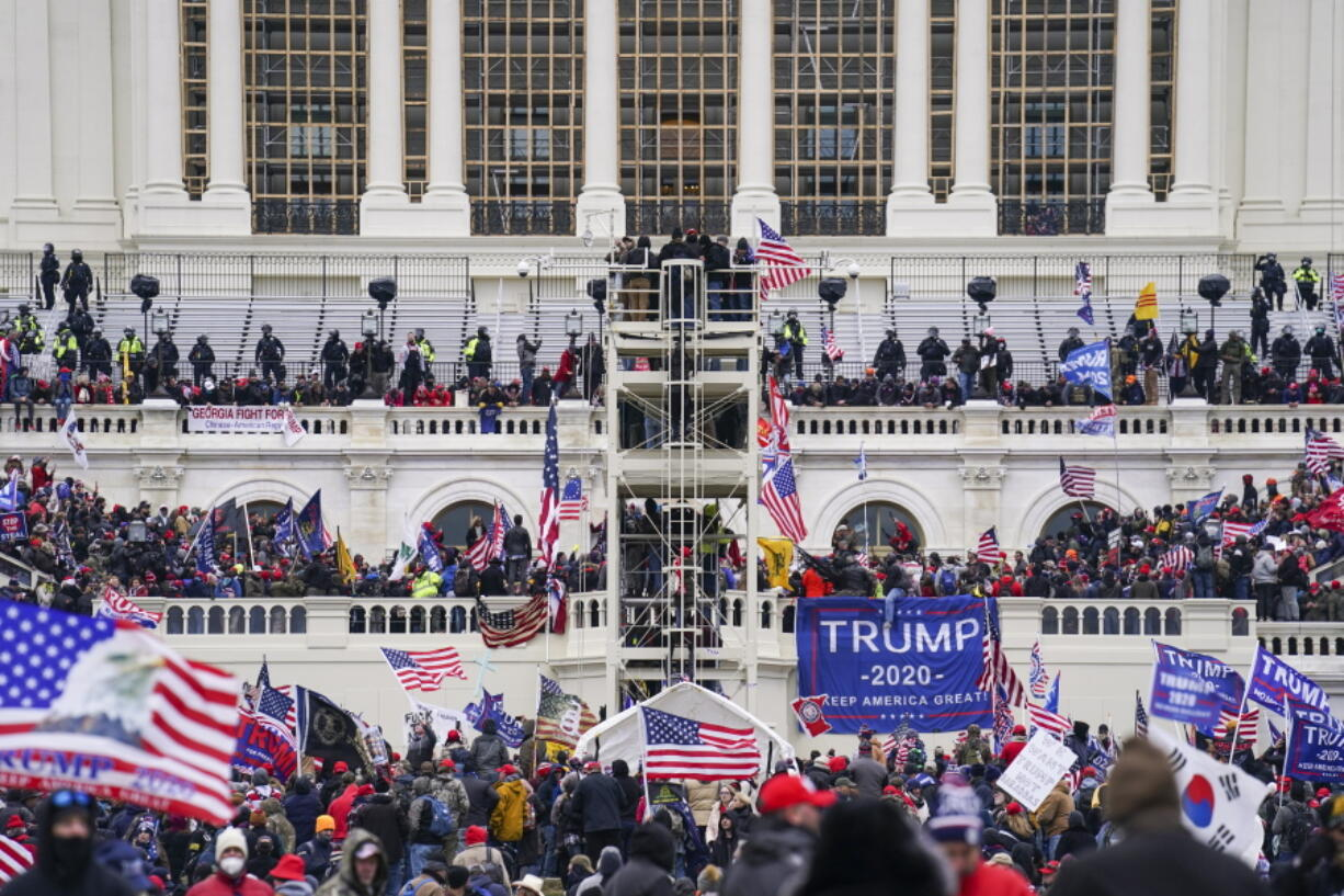 FILE - In this Jan. 6, 2021, file photo insurrectionists loyal to President Donald Trump breach the Capitol in Washington. Prosecutors secured the first guilty plea in the major case brought against members of the Oath Keepers extremist group in the attack on the U.S. Capitol, while an Indiana woman who became first person to be sentenced for the Jan. 6 riot avoided time behind bars.