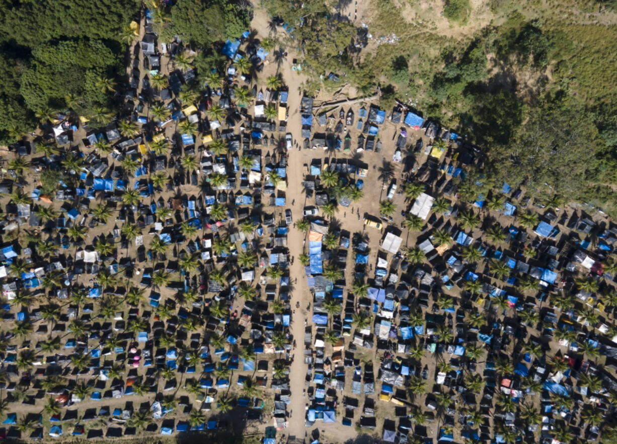 """FILE - In this May 26, 2021 file photo, tents and shacks cover land designated for a Petrobras refinery, called the """"First of May Refugee Camp,"""" which refers to the date the squatters camp sprung up amid the new coronavirus pandemic, in Itaguai, Rio de Janeiro state, Brazil. As Brazil hurtles toward an official COVID-19 death toll of 500,000, President Jair Bolsonaro has waged a campaign to downplay the virus's seriousness and keep the economy humming."""