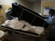 FILE - In this Jan. 9, 2021 file photo, transporters Miguel Lopez, right, Noe Meza prepare to move a body of a COVID-19 victim to a morgue at Providence Holy Cross Medical Center in the Mission Hills section of Los Angeles. The U.S. death toll from COVID-19 has topped 600,000, even as the vaccination drive has drastically slashed daily cases and deaths and allowed the country to emerge from the gloom. (AP Photo/Jae C.