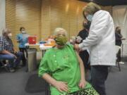 Kristy Stoos receives her COVID-19 inoculation March 17 at Grand Teton Mall in Idaho Falls, Idaho.