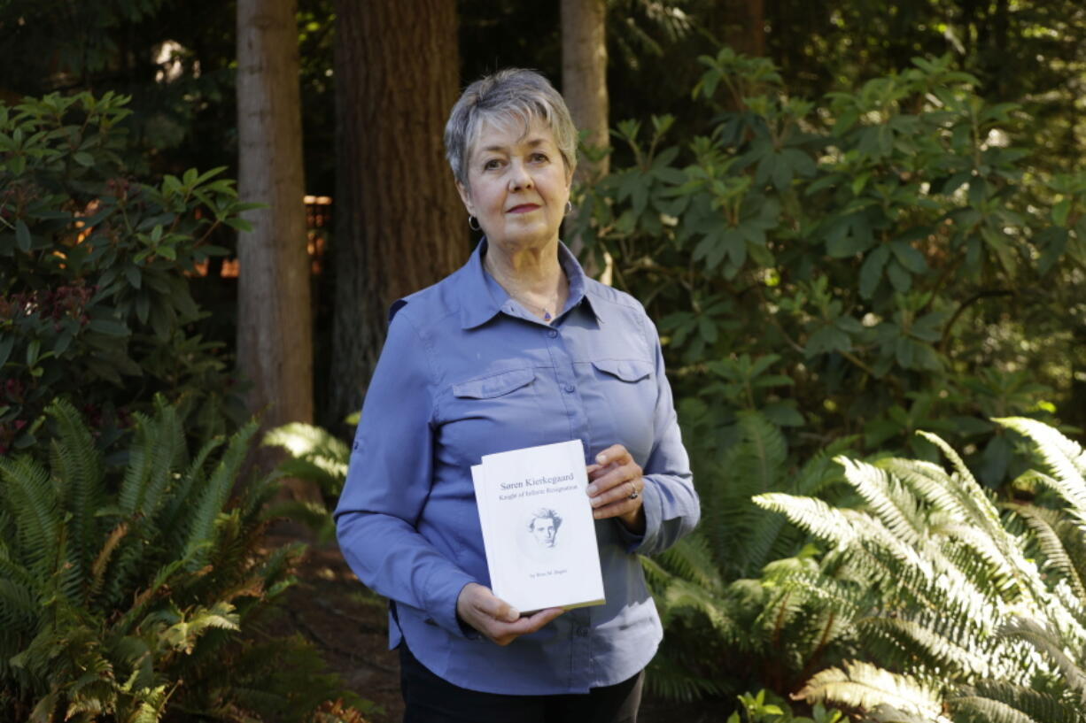 Karen McKnight stands in her backyard on Saturday, June 19, 2021, in Sammamish, Wash., holding two books written by her brother Ross Bagne of Cheyenne, Wyo.