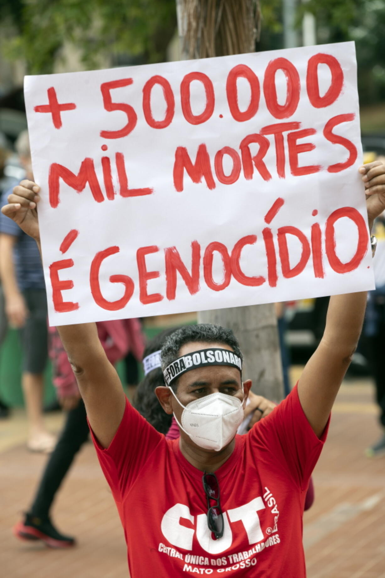 """A man, wearing a protective face mask, holds a sign with a message that reads in Portuguese; """"500,000 deaths is genocide"""", during a protest against Brazilian President Jair Bolsonaro and his handling of the pandemic and economic policies protesters say harm the interests of the poor and working class, in Cuiaba, Brazil, Saturday, June 19, 2021."""
