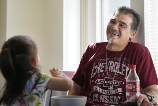Leroy Pascubillo smiles as he looks at his daughter, who was born addicted to heroin and placed with a foster family at birth, and talks about his journey regaining custody, May 10, 2021, in Seattle. Pascubillo, who had used drugs for the better part of four decades, was in a court-ordered in-patient drug rehab program when the pandemic first hit.