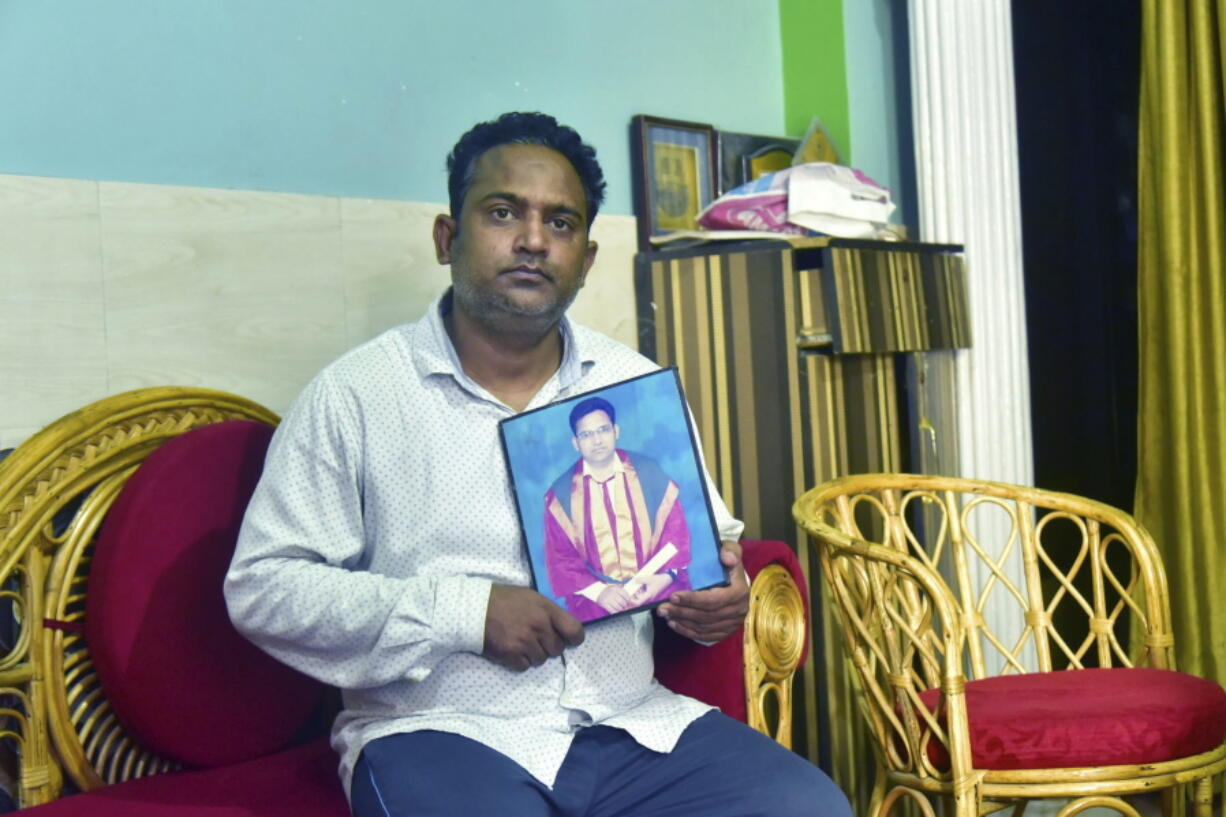 A relative holds a photograph of Dr. Jibraeil, assistant professor of history at Aligarh Muslim Uliversity, who died of COVID-19, in Aligarh, India, Saturday, June 12, 2021. Within just one month, the official Facebook page of Aligarh Muslim University, one of the topmost in India, published about two dozen obituaries of its teachers, all lost to the pandemic.