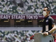 An official wears a face mask as he uses a starter pistol to signal the start a women's 100 meter heat at an athletics test event for the Tokyo 2020 Olympics Games at National Stadium in Tokyo, Sunday, May 9, 2021. Japan, seriously behind in coronavirus vaccination efforts, is scrambling to boost daily shots as the start of the Olympics in July closes in.