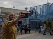 FILE - In this Feb. 23, 2021, file photo, Palestinians take a selfie after receiving the coronavirus vaccine from an Israeli medical team at the Qalandia checkpoint between the West Bank city of Ramallah and Jerusalem. Israel said Friday, June 18, 2021 it will transfer around 1 million doses of soon-to-expire coronavirus vaccines to the Palestinian Authority in exchange for a similar number of doses the Palestinians expect to receive later this year.
