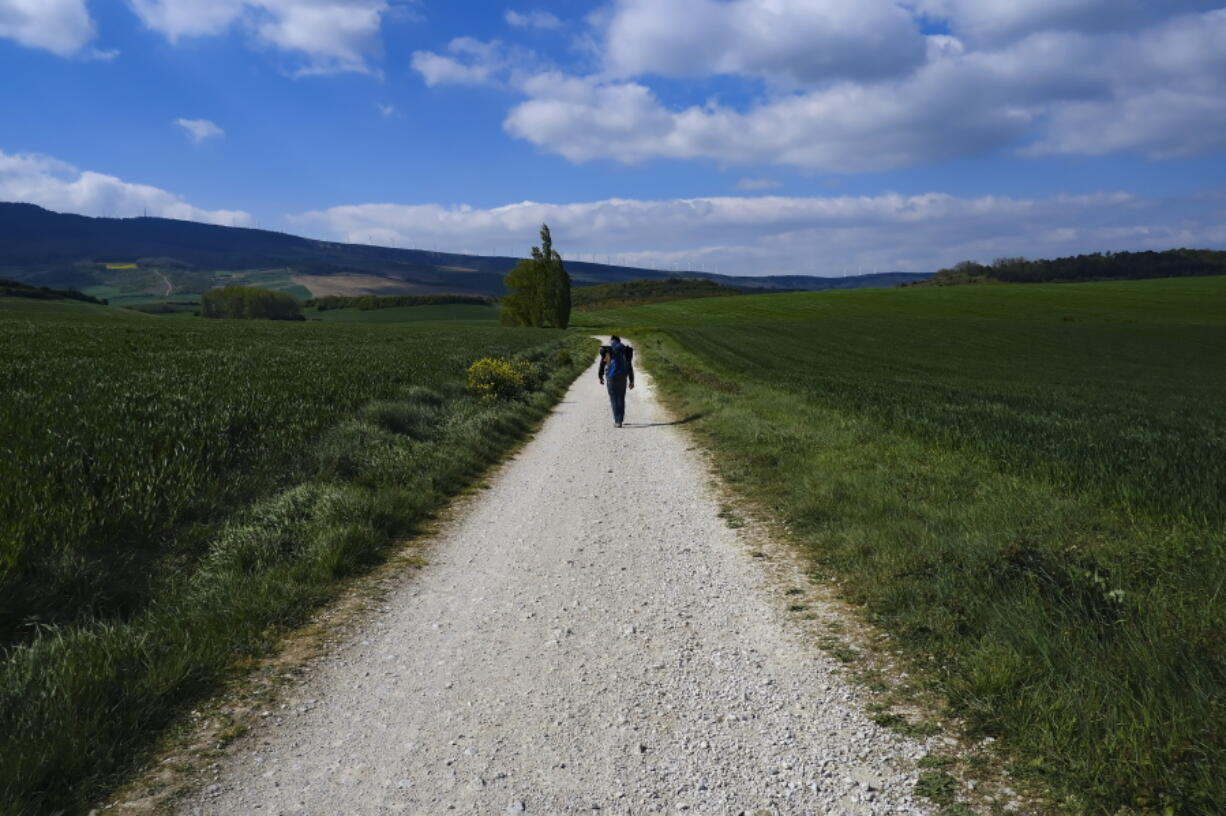 """Martim Thomas, 41, from Switzerland, walks along a path during a stage of """"Camino de Santiago"""" or St. James Way near Pamplona, northern Spain, Thursday, April 14, 2021. The pilgrims are trickling back to Spain's St. James Way after a year of being kept off the trail due to the pandemic. Many have committed to putting their lives on hold for days or weeks to walk to the medieval cathedral in Santiago de Compostela in hopes of healing wounds caused by the coronavirus."""