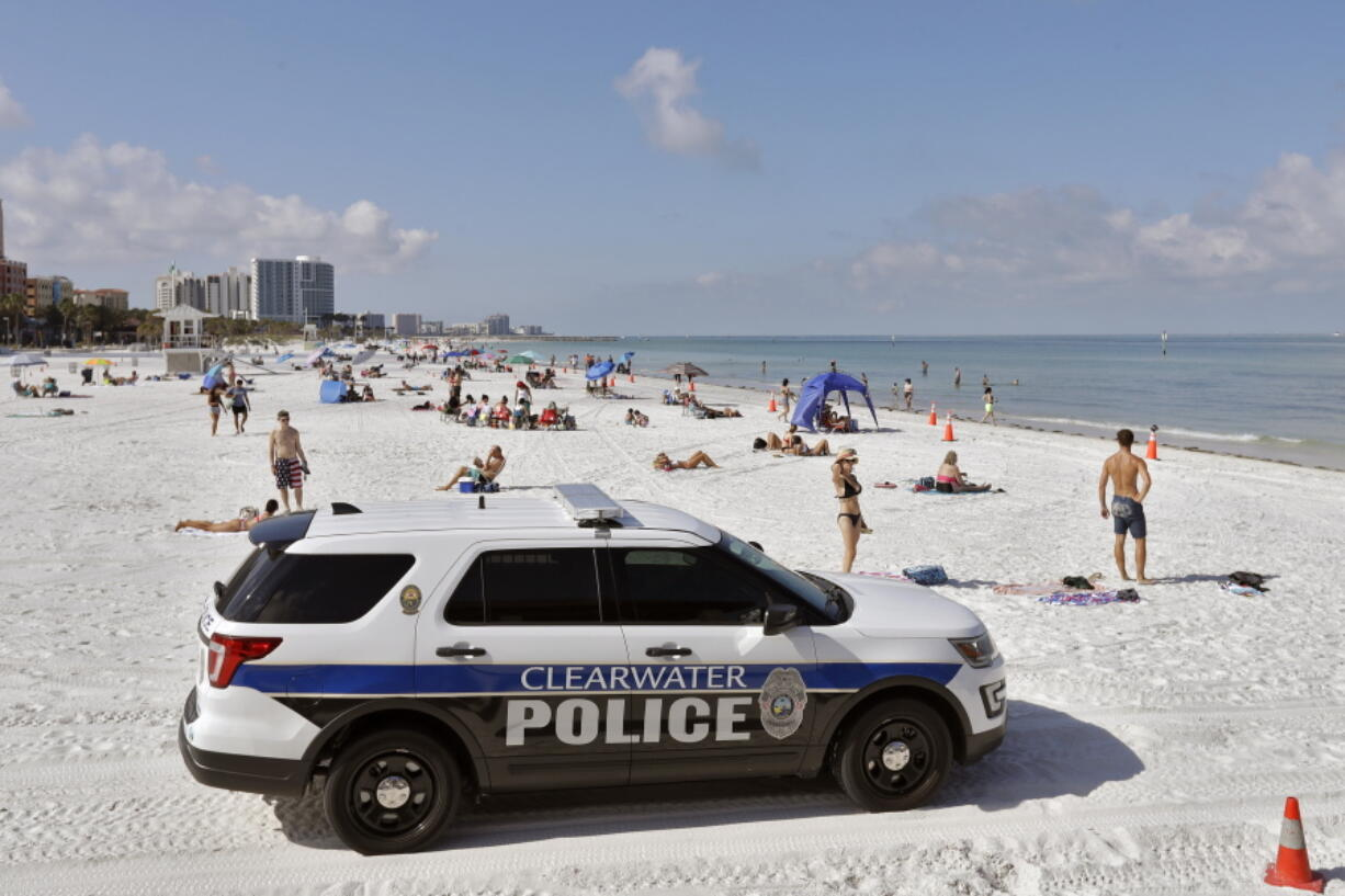 FILE - In this Monday, May 4, 2020 file photo, police officers patrol the area after Clearwater Beach officially reopened to the public in Clearwater Beach, Fla. Florida is among several states that amplified their 2021-2022 budgets with at least part of their share of a $195 billion state aid package from the recent American Rescue Plan Act signed by President Joe Biden. The state's record $101.5 billion budget is up roughly 11%, with bonuses for teachers, police and firefighters, and new construction projects at schools and colleges.