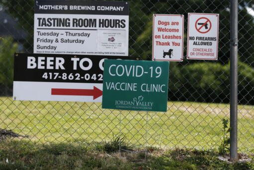 Signs hang on a fence for Mother's Brewing Company's COVID-19 vaccine clinic in partnership with the Springfield-Greene County Health Department and Jordan Valley Community Health Center on Tuesday, June 22, 2021, in Springfield, Mo. As the U.S. emerges from the COVID-19 crisis, Missouri is becoming a cautionary tale for the rest of the country: It is seeing an alarming rise in cases because of a combination of the fast-spreading delta variant and stubborn resistance among many people to getting vaccinated.