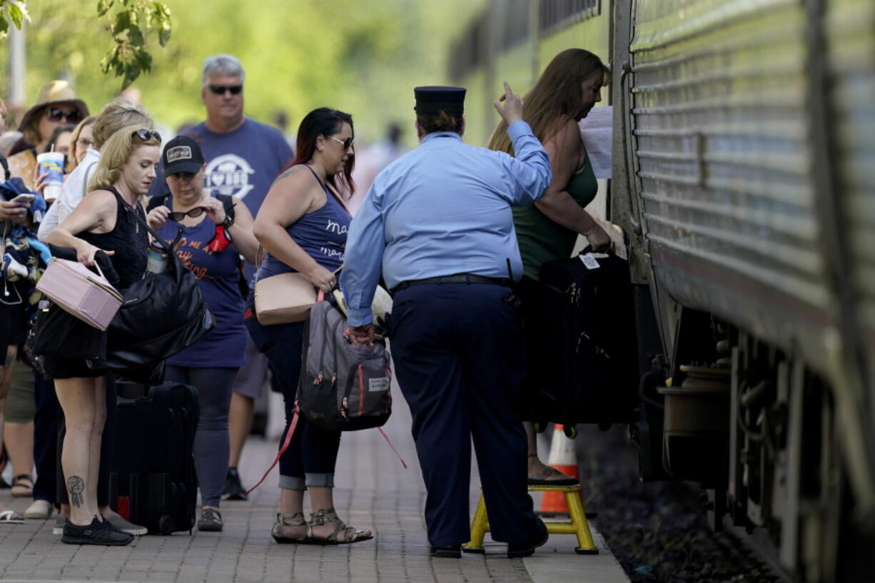 FILE - In this June 11, 2021, file photo, passengers board a Missouri River Runner Amtrak train in Lee's Summit, Mo. As the U.S. emerges from the COVID-19 crisis, Missouri is becoming a cautionary tale for the rest of the country: It is seeing an alarming rise in cases because of a combination of the fast-spreading delta variant and stubborn resistance among many people to getting vaccinated.