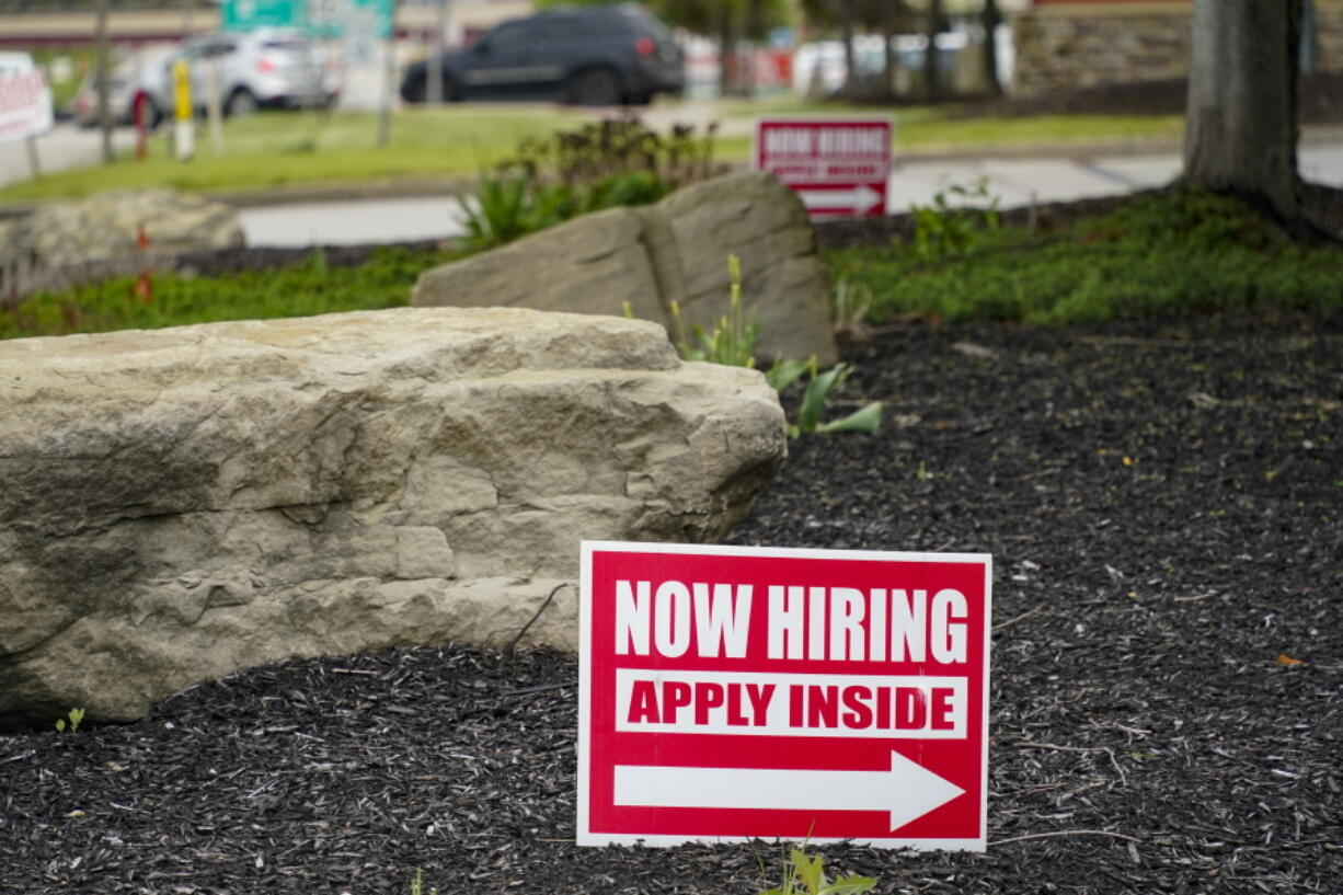 This May 5, 2021 photo shows hiring signs posted outside a gas station in Cranberry Township, Butler County, Pa. The number of Americans applying for unemployment benefits dropped last week,  reported Thursday, June 24, a sign that layoffs declined and the job market is improving.