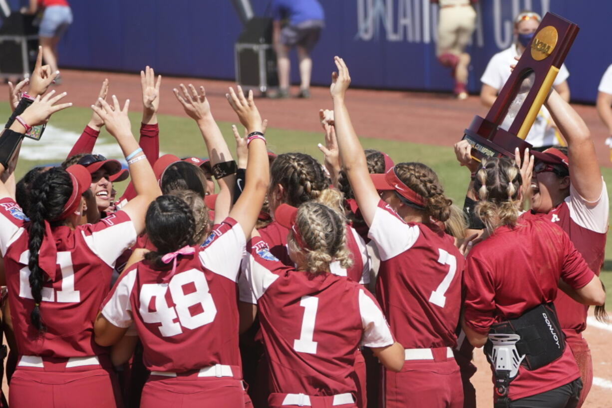 Oklahoma players celebrate with the trophy after defeating Florida State in the final game of the NCAA Women's College World Series softball championship series Thursday, June 10, 2021, in Oklahoma City.