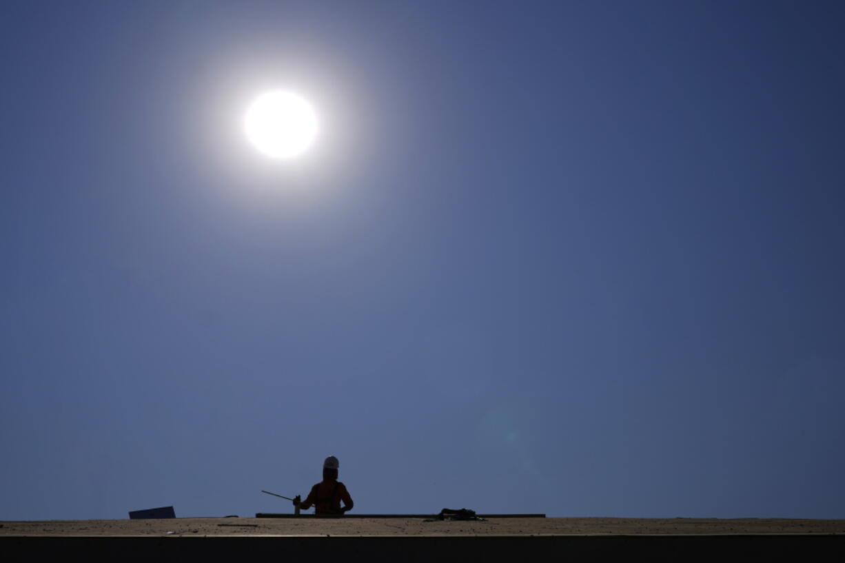 A roofer works on a new roof in a housing development while the sun beats down on him as the heat wave continues Thursday in Phoenix. (Ross D.