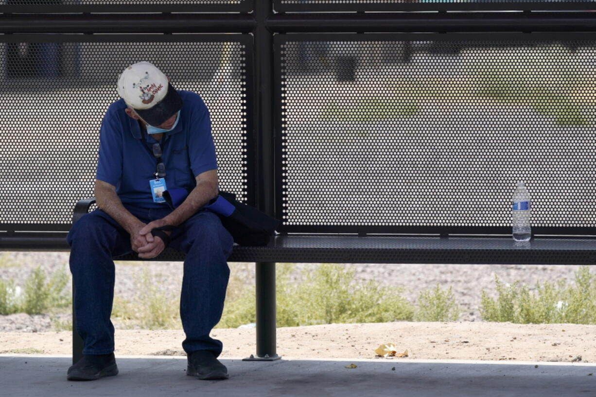 A person waits for a bus in the shade as the heat wave in the Western states continues Thursday, June 17, 2021, in Phoenix. (AP Photo/Ross D.