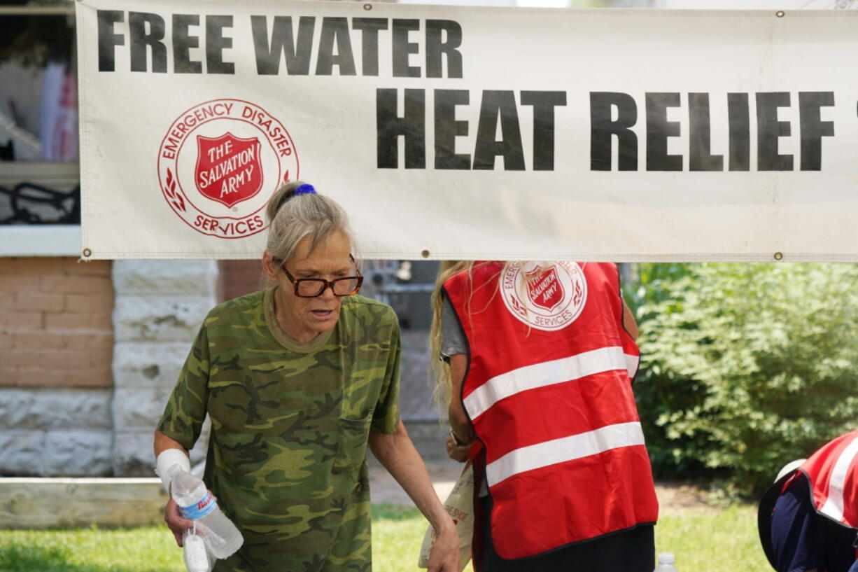 A pedestrian takes a bottle of water at a Salvation Army hydration station during a heatwave as temperatures hit 115-degrees, Tuesday, June 15, 2021, in Phoenix. (AP Photo/Ross D.